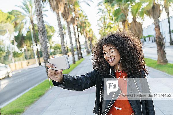 Porträt einer lächelnden jungen Frau  die mit einem Smartphone Selbsthilfe betreibt