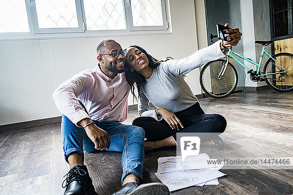 Smiling businessman and businesswoman sitting on the floor taking a selfie