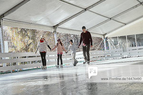 Family with two kids ice skating on the ice rink