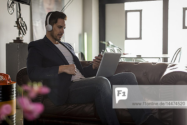Man with headphones sitting on couch using cell phone and laptop