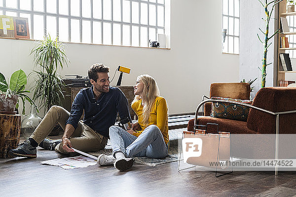 Smiling businessman and businesswoman sitting on the floor discussing documents in loft office
