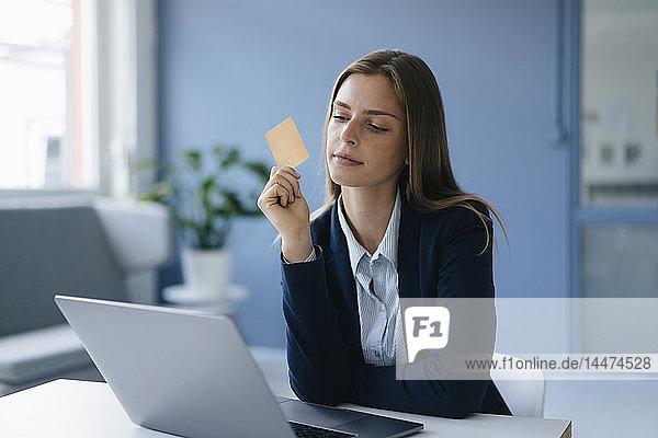 Junge Geschäftsfrau macht Online-Zahlungen mit ihrer Kreditkarte
