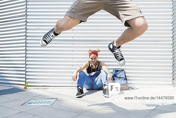 Junge Frau beobachtet ihren Freund  wie er in die Luft springt