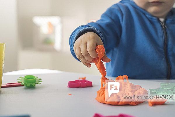 Hand eines kleinen Mädchens  das Modelliermasse nimmt  Nahaufnahme