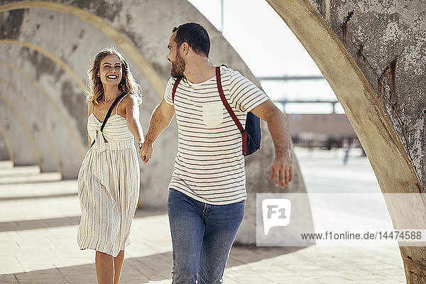 Spain  Andalusia  Malaga  carefree tourist couple running under an archway in the city