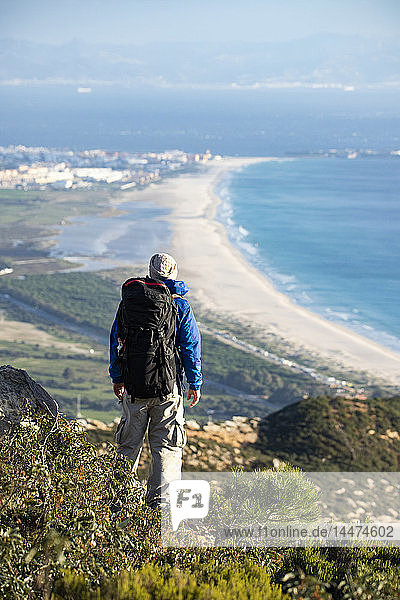 Spain  Andalusia  Tarifa  man on a hiking trip at the coast looking at view