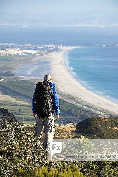 Spanien  Andalusien  Tarifa  Mann auf einer Wanderung an der Küste mit Blick auf die Aussicht