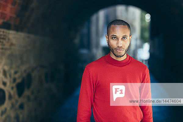 Portrait of young man in an underpass wearing red pullover