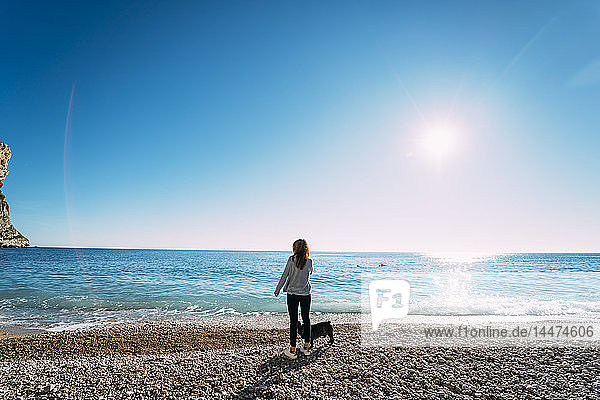 Spanien  Alicante  Benitachell  Rückenansicht einer Frau  die mit ihrem Hund am Strand steht und auf die Aussicht schaut