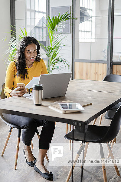 Young businesswoman working at desk in loft office
