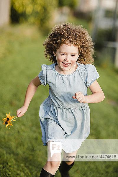 Glückliches kleines Mädchen rennt auf einer Wiese im Garten