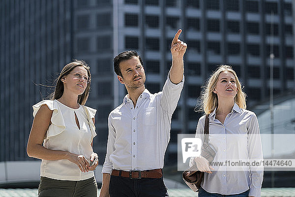 Businessman with colleagues in the city pointing his finger