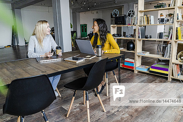 Two happy young businesswomen sitting at conference table in loft office