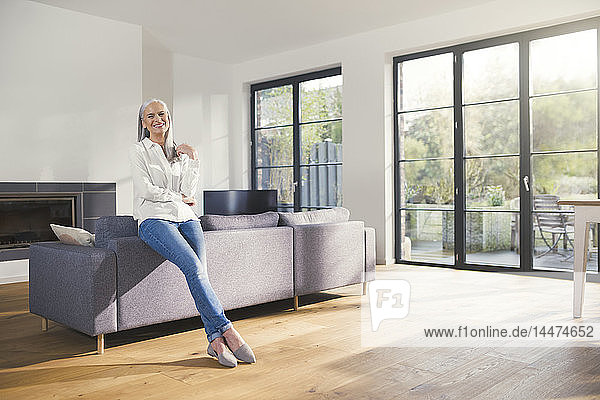 Ältere Frau  die im Wohnzimmer an der Couch steht