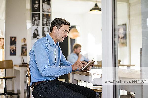 Geschäftsmann am Tisch sitzend mit Tablette
