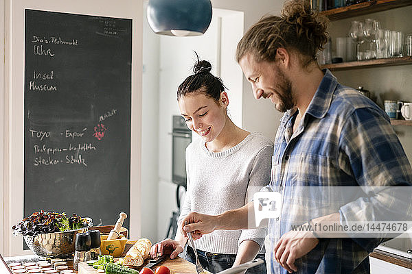 Young couple preparing food together  tasting spaghetti