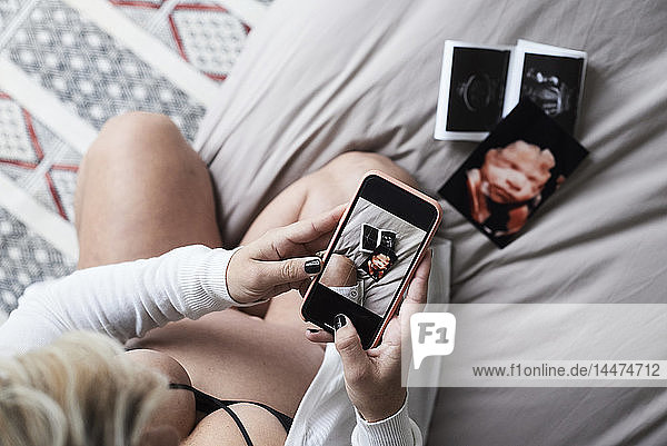 Pregnant woman at home sitting on bed taking pictures of ultrasound images