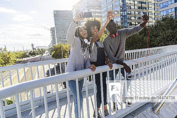 Freunde stehen auf einer Brücke und nehmen sich selbst