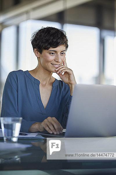 Geschäftsfrau sitzt mit Laptop am Schreibtisch im Büro