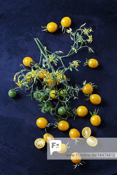 Whiole und in Scheiben geschnittene Tomaten 'Blondköpfchen' auf dunklem Grund