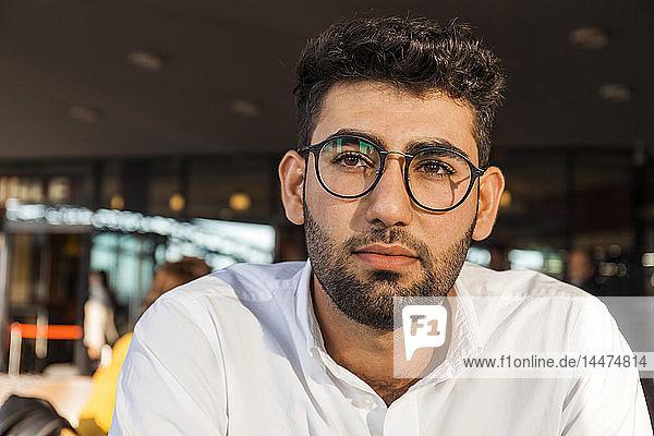 Porträt eines nachdenklichen jungen Geschäftsmannes mit Bart und Brille im Straßencafé