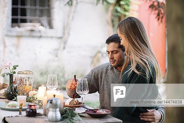 Romantisches Paar beim Essen bei Kerzenlicht am Gartentisch