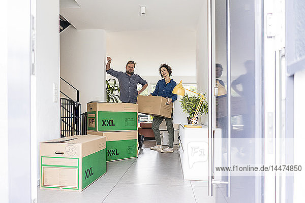 Porträt eines Paares im neuen Zuhause mit Pappkartons