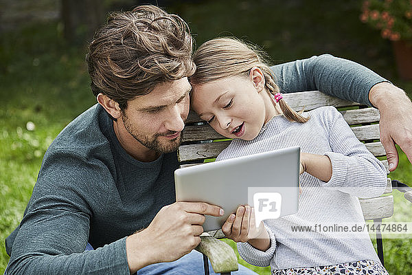 Father and daughter using tablet together in garden