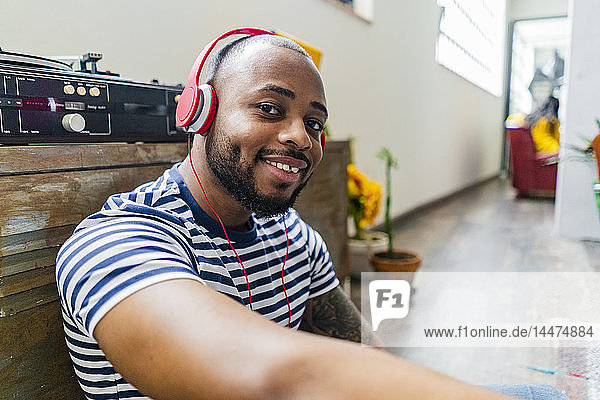 Portrait of smiling young man with headphones sitting on floor in a loft