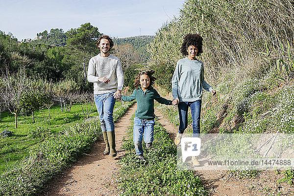 Glückliche Familie auf dem Land  die Händchen hält