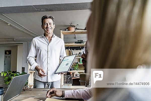 Smiling businessman leading a presentation in loft office