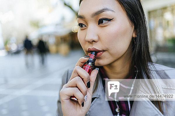 Junge Frau raucht elektronische Zigarette