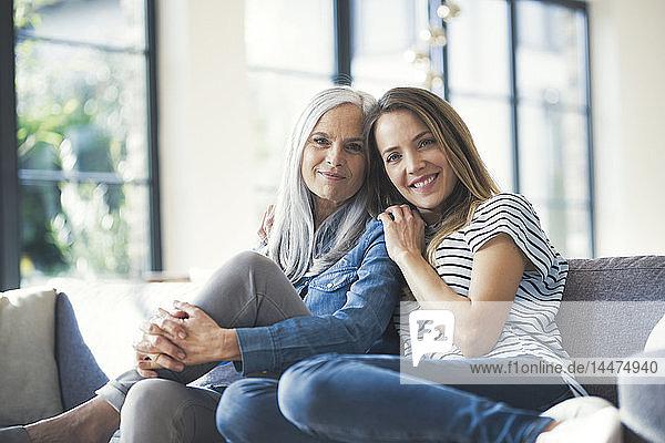 Tochter hält Mutter im Arm und sitzt auf dem Sofa