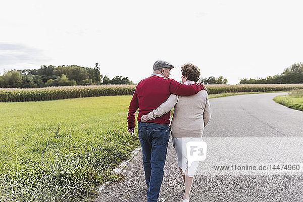 Älteres Ehepaar bei einem Spaziergang in ländlicher Landschaft