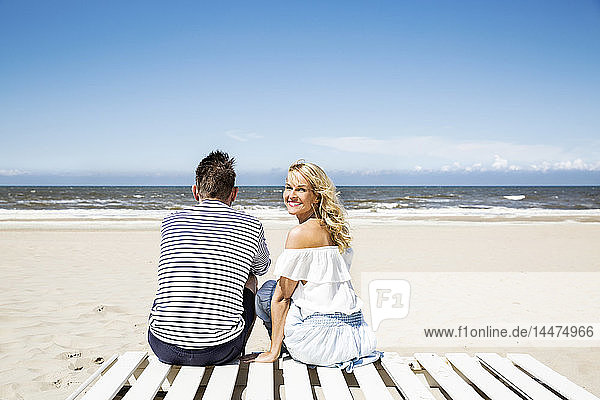 Couple sitting on boardwalk on the beach