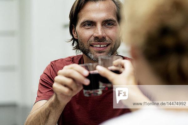 Glückliches Paar stößt mit Rotwein an
