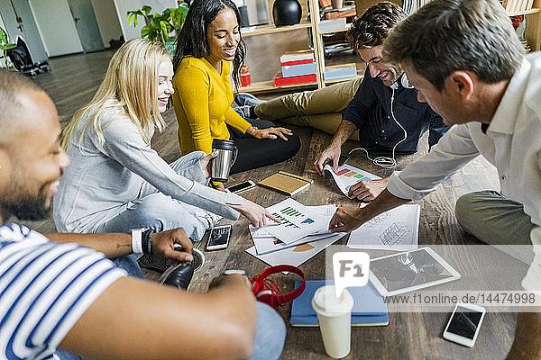 Fröhliches Geschäftsteam sitzt auf dem Boden und bespricht Dokumente im Loft-Büro