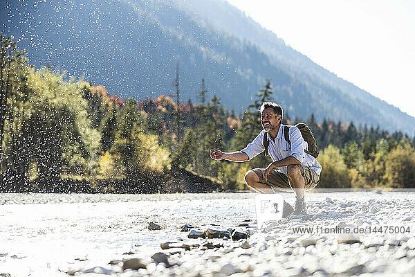 Österreich  Alpen  Mann auf Wanderung mit Abkühlungspause an einem Bach