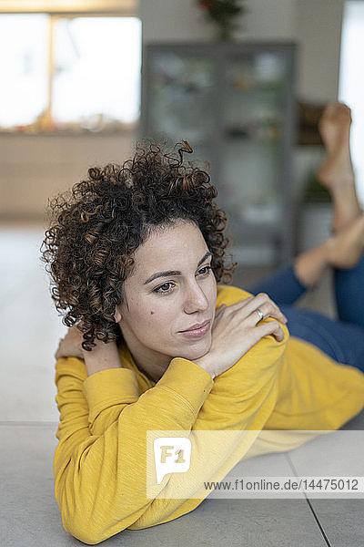 Frau liegt zu Hause auf dem Boden