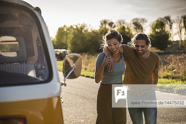 Affectionate couple walking on the road with arms around  next to their camper
