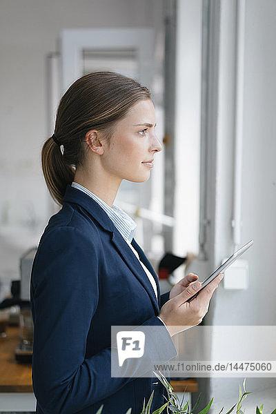 Junge Geschäftsfrau steht am Fenster und benutzt ein digitales Tablet