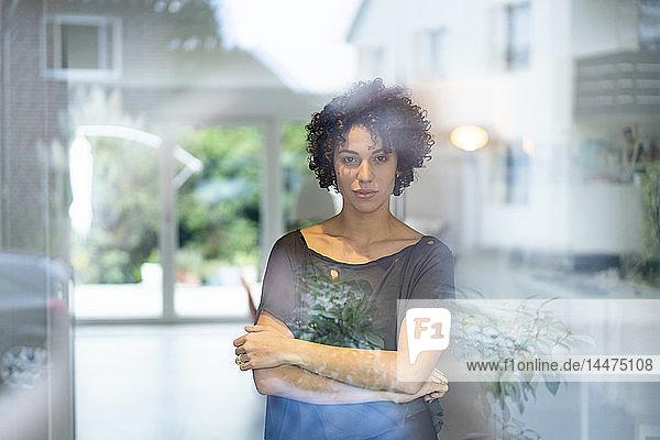 Porträt einer Frau  die zu Hause hinter dem Fenster steht