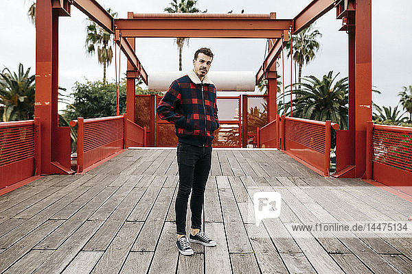 Young man with casual clothes on a red bridge looking at camera