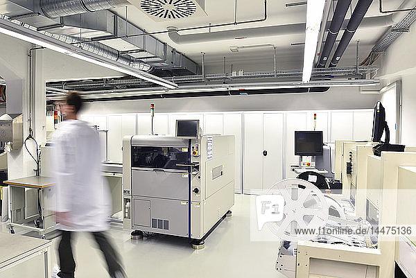 Mann geht in einer Fabrik zur Herstellung von Leiterplatten für die Elektronikindustrie