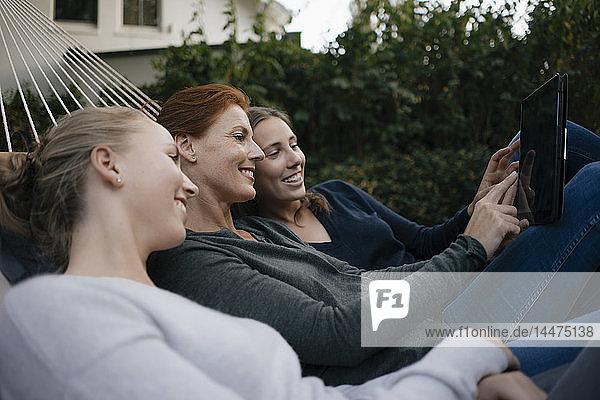 Glückliche Mutter mit zwei Teenager-Mädchen  die im Herbst in der Hängematte im Garten liegen und Tabletten benutzen