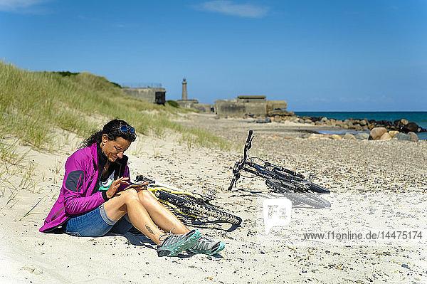 Dänemark  Jütland  Skagen  Grenen  Frau sitzt am Strand neben dem Fahrrad und benutzt das Handy