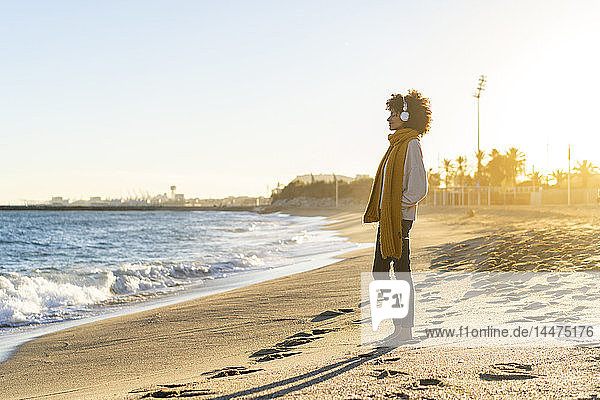 Frau am Strand  die Kopfhörer trägt und Musik hört