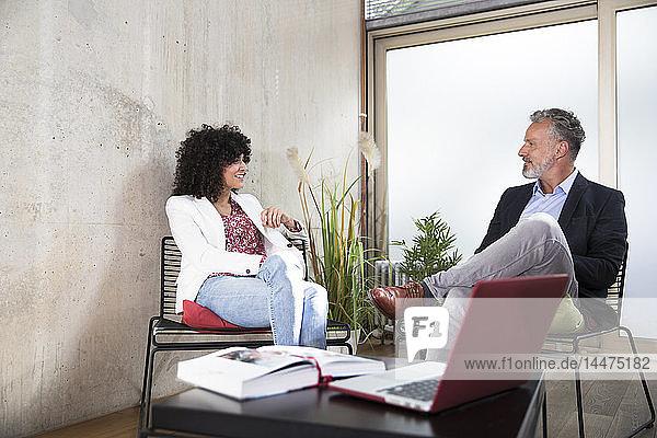 Geschäftsmann und Geschäftsfrau sitzen in einem Loft an einer Betonwand und lächeln
