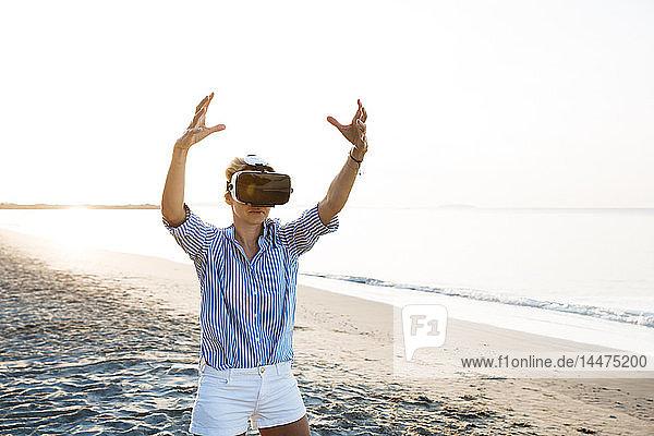 Blonde Frau macht eine Art Yoga-Übungen an einem Strand in Thailand mit einer 3D-Brille für virtuelle Realität
