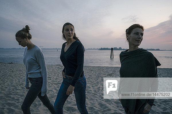 Deutschland  Hamburg  Mutter mit zwei Teenager-Mädchen  die abends am Strand am Elbufer spazieren gehen